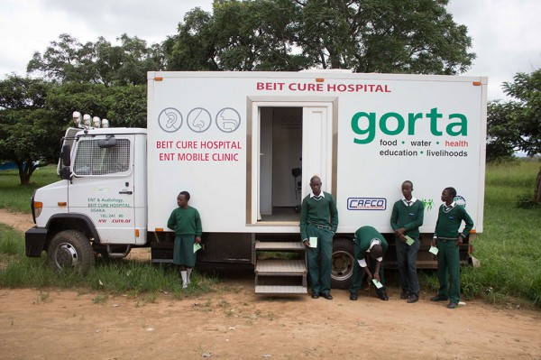 Secondary school students wait outside the mobile clinic to see CURE's ENT surgeon, Dr. Ute Froeschl.