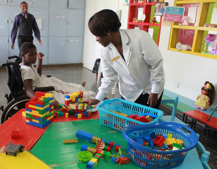 Kellen, CURE Kenya's ward manager, helps Rebecca settle in at the playroom