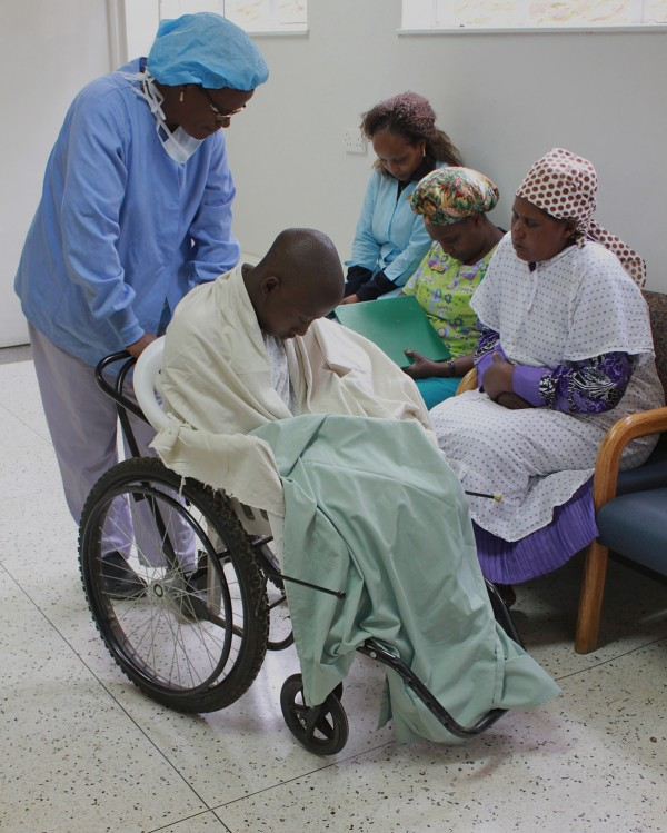 Terry, Gladys, and Phillis pray with Jeff and his mother just before he is wheeled into the OR for surgery