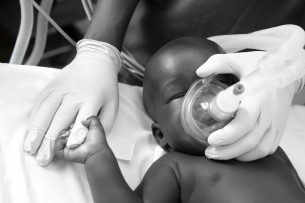 Desire holds onto Thomas' finger as he administers an anesthetic before her operation for hydrocephalus.