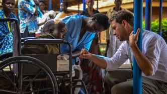 Derek Johnson with a child at CURE Uganda