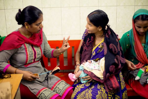 Counselor with a mother and baby at a CURE clubfoot clinic