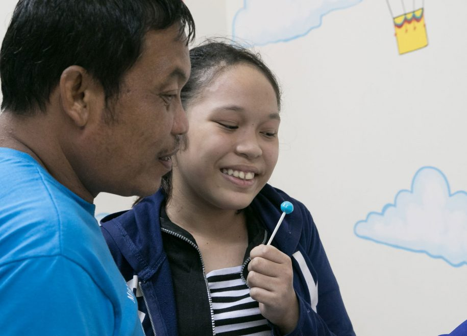 Charmaine and dad William share a smile as they see her clubfoot-free feet for the first time.