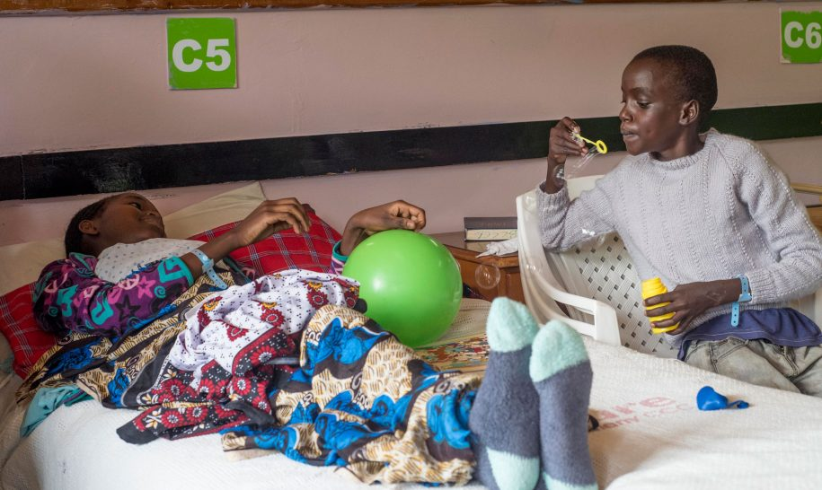 Daudi meets Sharon at her bedside to play with bubbles.