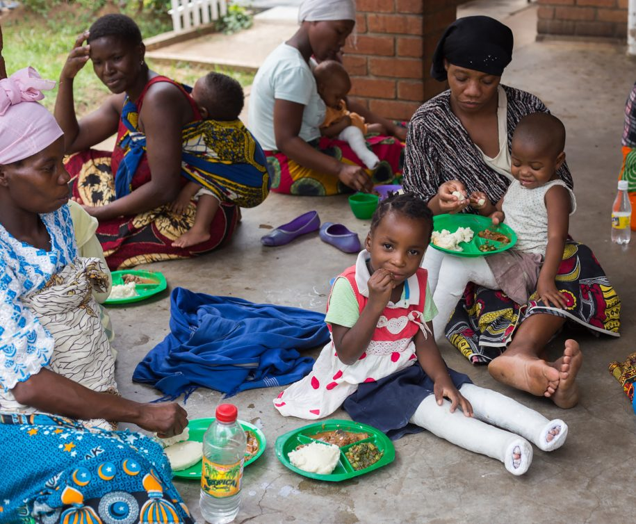 Aisha eats some delicious nsima and beef at the kitchen with the other CUREkids and their moms!