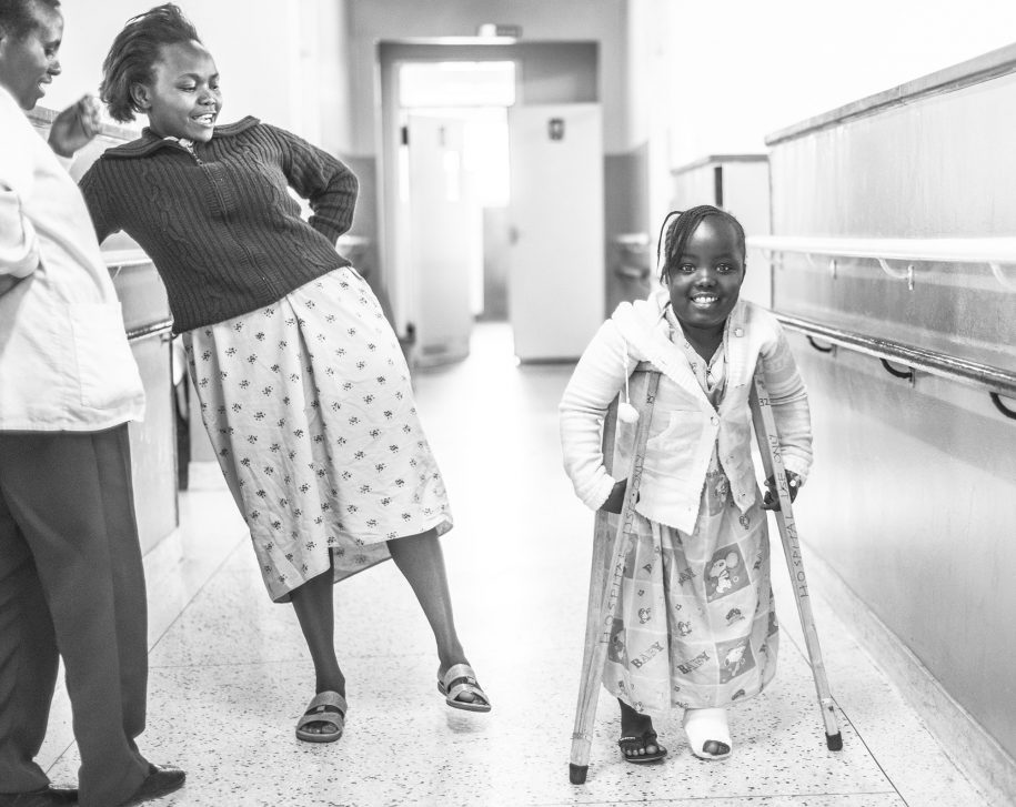 Christine's mother proudly shows her friend at the ward her daughter walking with crutches after surgery.