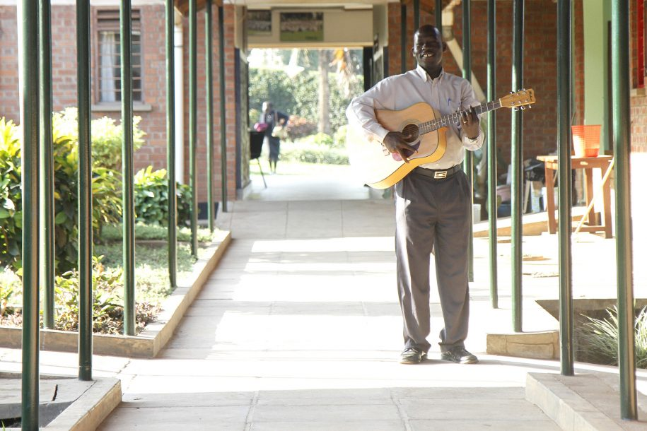 Pastor Simon Peter walks down the corridor with is guitar.
