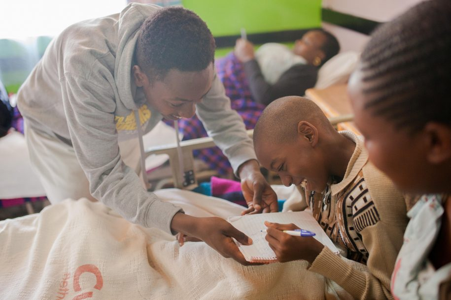 Elvis, our CUREkids Intern, shares his notebook with Moses so that Moses can practice his writing.