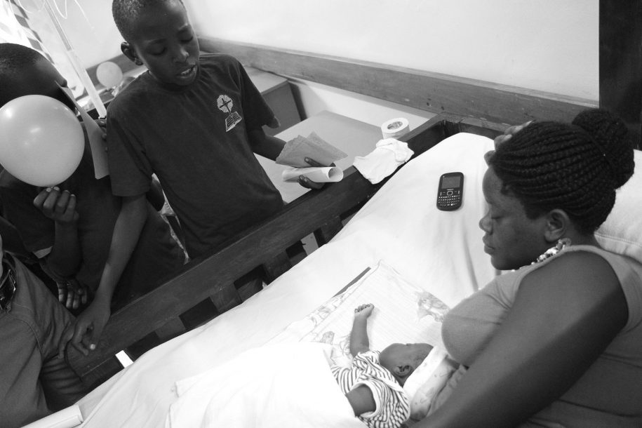 Tony prays for Gloria and her mother. He was one of 15 children from New Life Church who came to CURE to pray for the patients in the ward.