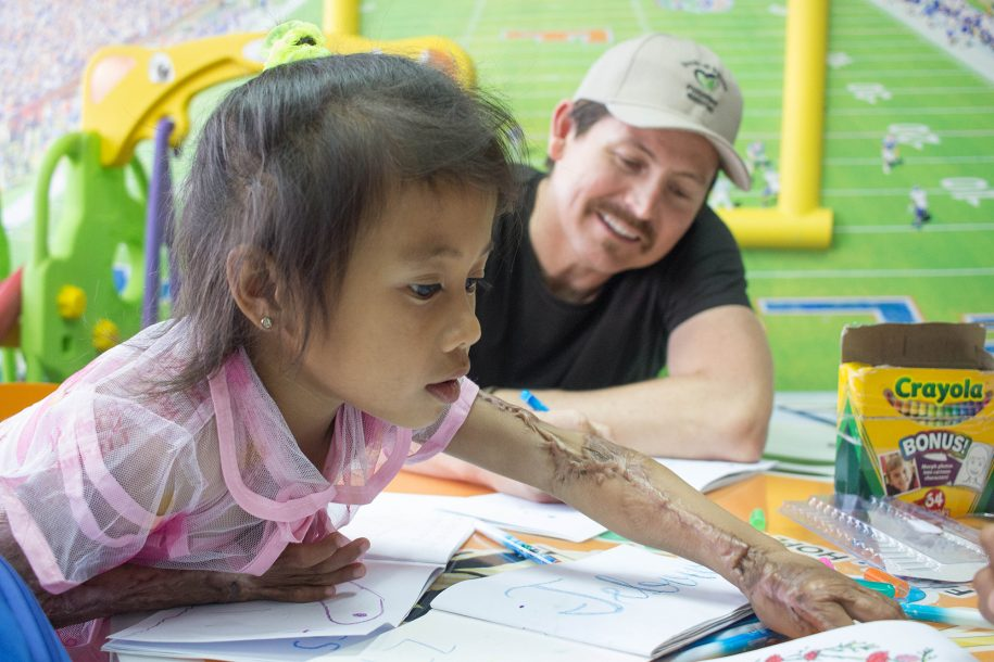 Chad from Switchfoot spends time with Jocy while doing art work in the playroom.