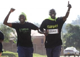 Andrew a nurse at CURE Uganda and Moses a social worker at CURE Uganda hold hands and celebrate as they run the Eastern Marathon for Vulnerable Children May 6.