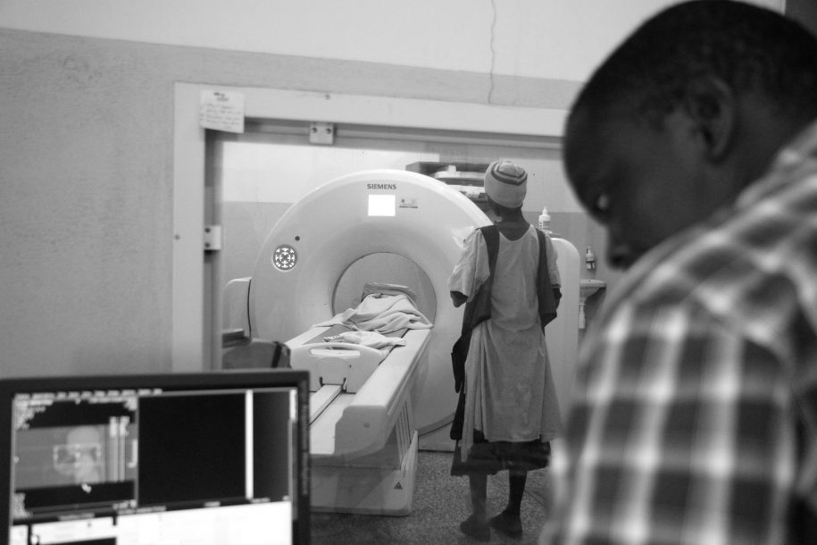 Simon watches the monitor as he performs a CT-scan. Inside the CT-scan room, Annet watches her son Aaron get scanned.