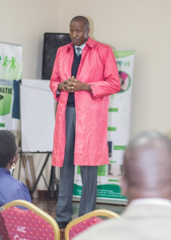 Rev. Justus Mutuku using a raincoat as an example of how tailors have designs in their minds, that even without us telling them how we want something to look, they come up with an idea and give us something we can work with. This is the same way that God had an idea and designed a manual (the Bible) which we are supposed to use every day.